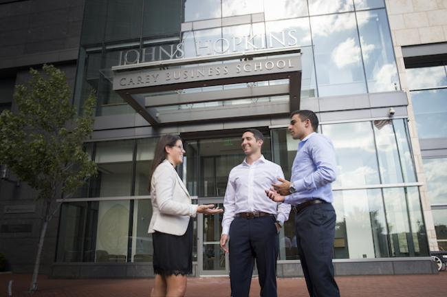 Three students stand in front of the entrance to the Johns Hopkins Carey Business School