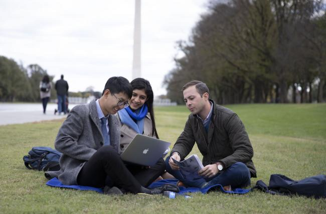 3 students siting on lawn in front of the Washington monument.