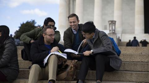 students studying together in front of a monument in washington, dc