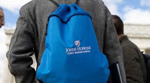 man wearing a johns hopkins carey business school branded backpack