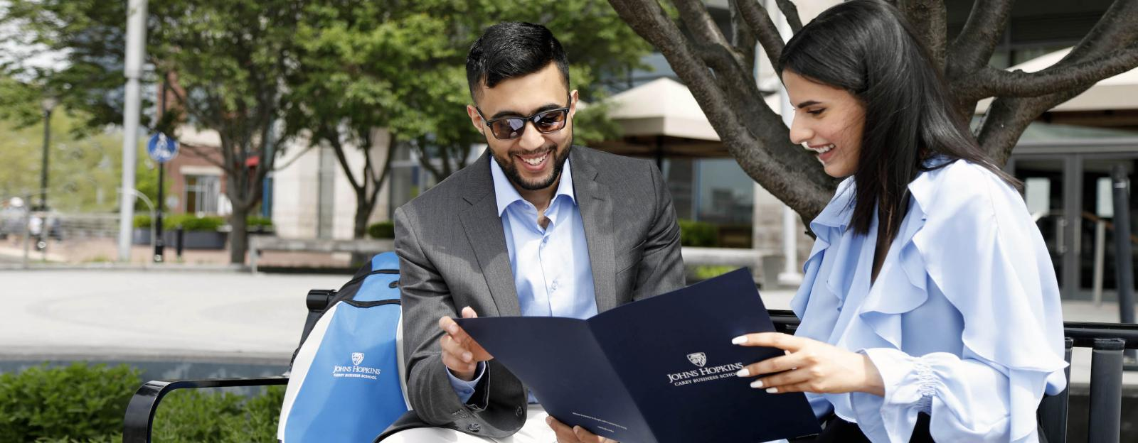 two students look down at a johns hopkins carey business school folder