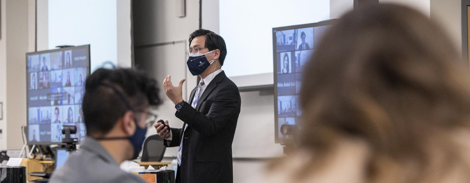lecture in a hybrid classroom with the professor and students with masks